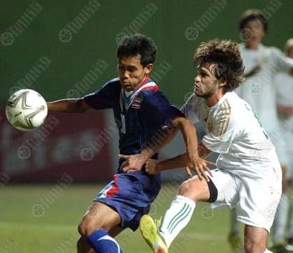 ธีรศิลป์ แดงดา (ซ้าย) กองหน้าทีมไทย เบียดแย่งบอลกับแข้งเติร์กเมนิสถานในเกมรอบ 16 ทีมสุดท้าย